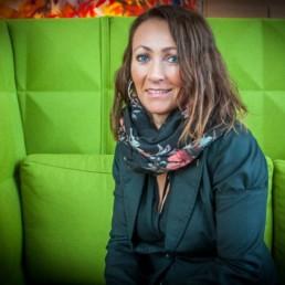 Lena Brunes Hippe sitter i grønn sofa. Foto: Christine Karijord